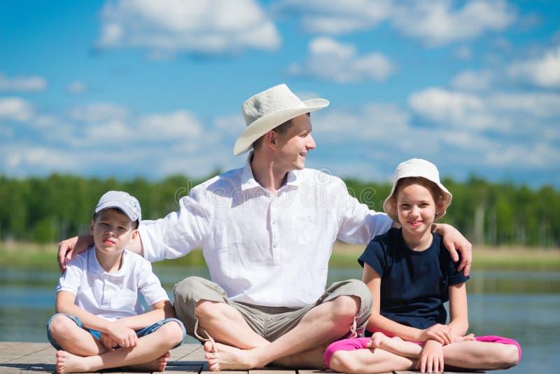 Il padre con il derivato ed il figlio si siede su un bello pilastro sul lago immagine stock libera da diritti