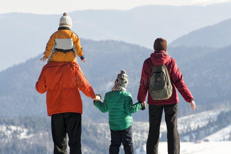 Il padre con il figlio sulle spalle, la madre ed il figlio stanno indietro contro lo sfondo delle montagne innevate Giorno solegg immagine stock