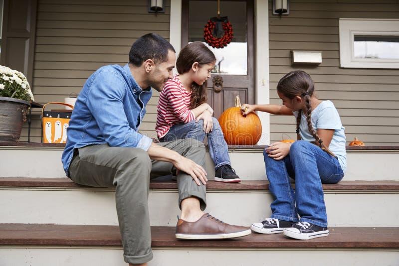 Il padre And Daughters Drawing affronta sulla zucca di Halloween immagini stock libere da diritti