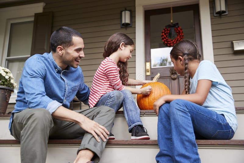Il padre And Daughters Drawing affronta sulla zucca di Halloween immagine stock