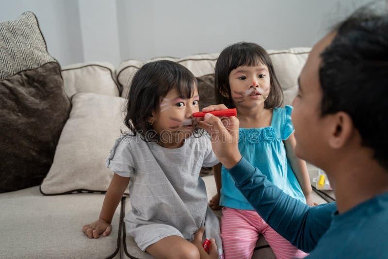 Il padre dipinge sua figlia due nel fronte immagine stock