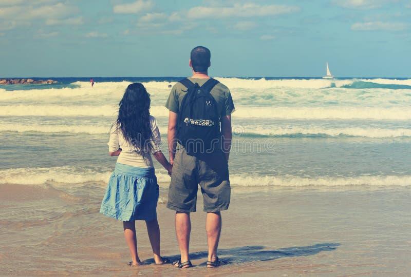 Il padre e la figlia godono della spiaggia con il bot della vela sull'orizzonte fotografie stock