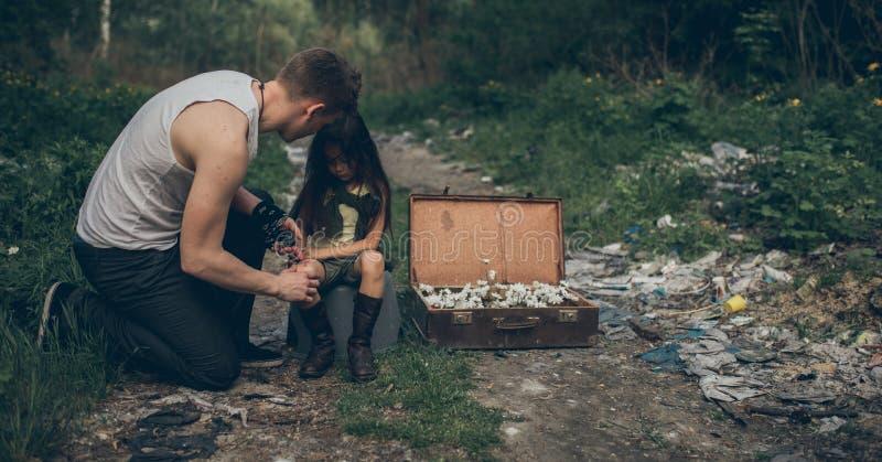 Il padre e la figlia senza tetto sono nella discarica accanto ad una valigia con i fiori dentro fotografia stock libera da diritti