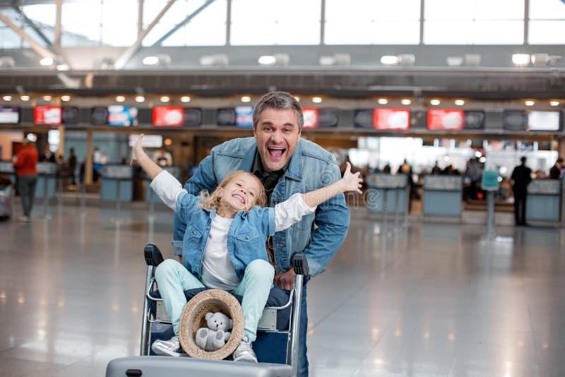 Il padre e la figlia stanno giocando in terminale fotografia stock