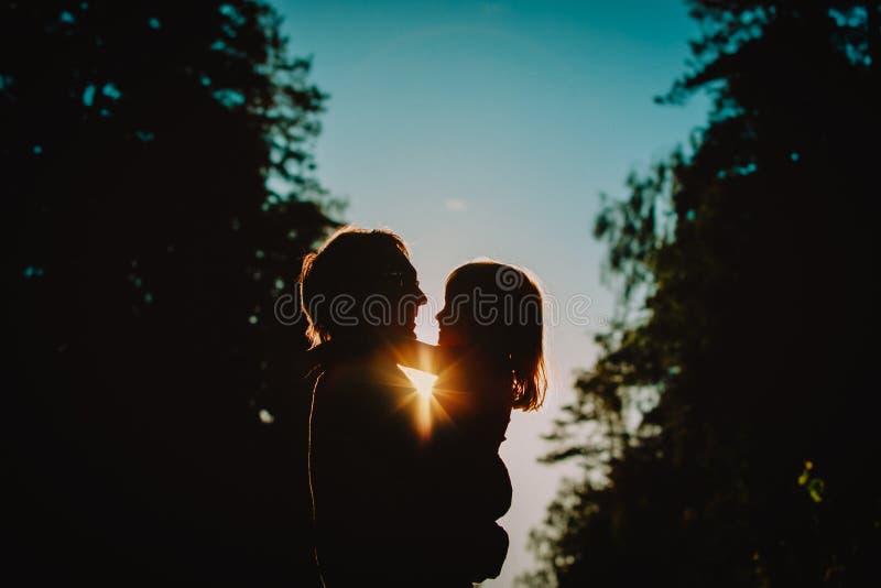 Il padre e la piccola figlia profila il gioco al tramonto immagini stock libere da diritti