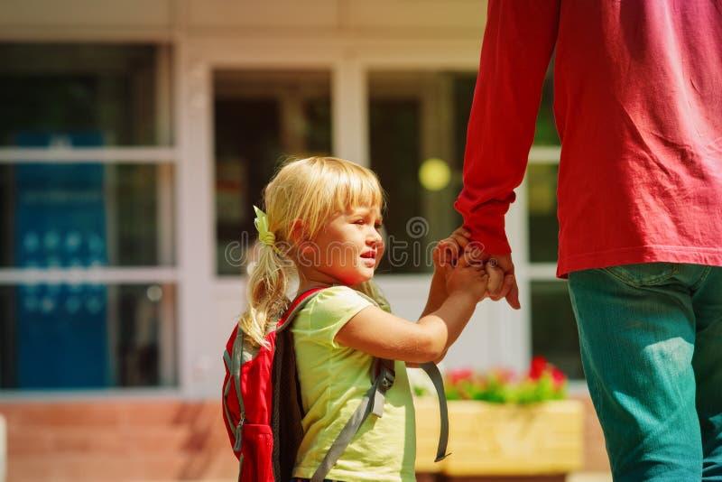 Il padre e la piccola figlia vanno a scuola o la guardia fotografie stock libere da diritti