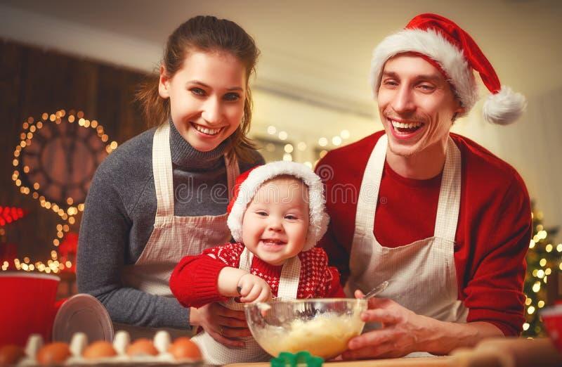 Il padre ed il bambino della madre della famiglia cuociono i biscotti di natale fotografie stock