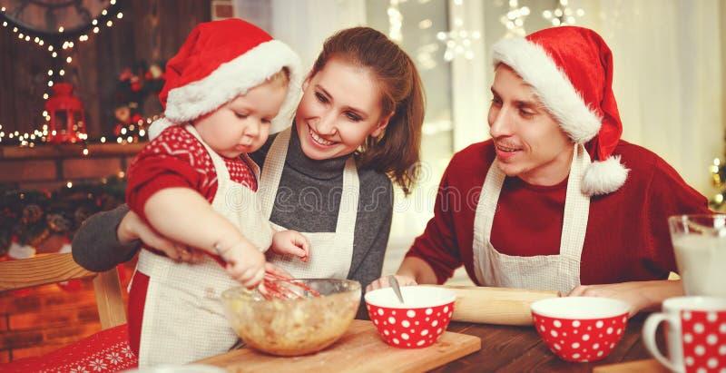 Il padre ed il bambino della madre della famiglia cuociono i biscotti di natale fotografia stock