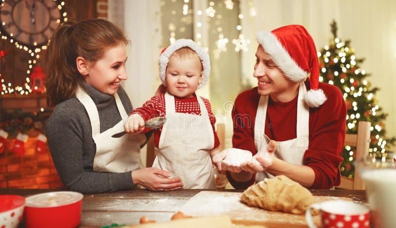 Il padre ed il bambino della madre della famiglia cuociono i biscotti di natale immagini stock libere da diritti