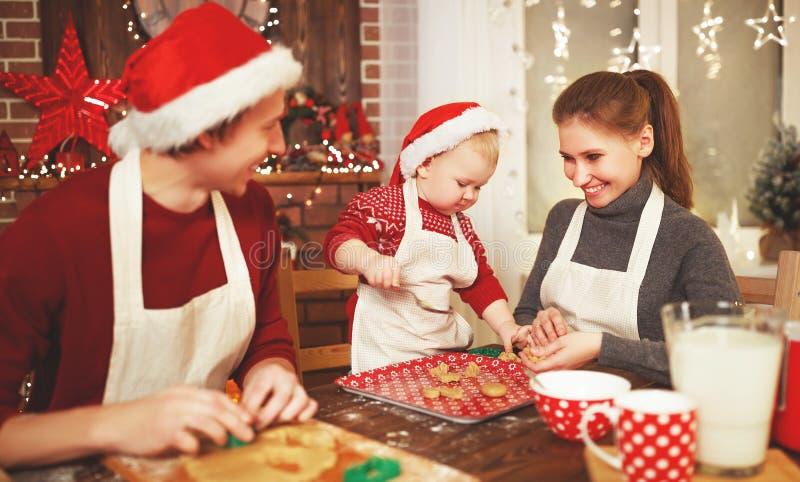 Il padre ed il bambino della madre della famiglia cuociono i biscotti di natale fotografie stock libere da diritti