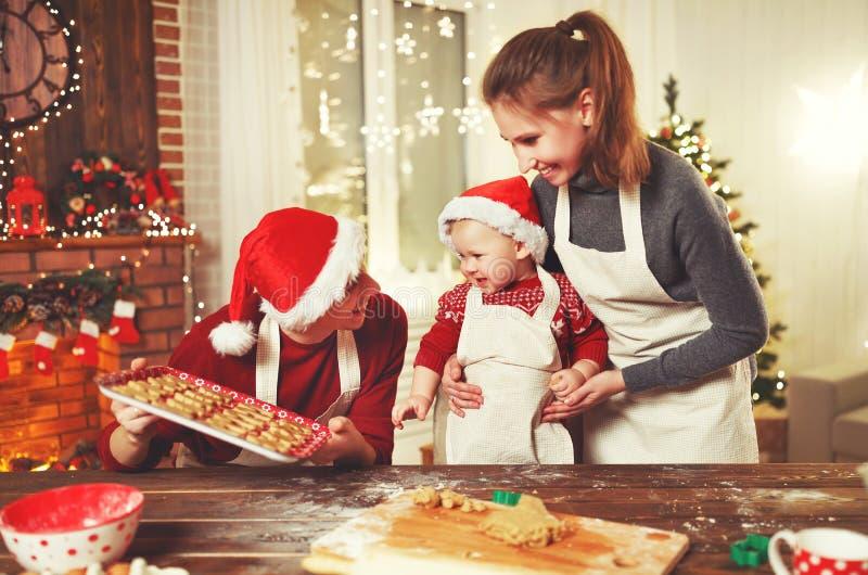 Il padre ed il bambino della madre della famiglia cuociono i biscotti di natale immagine stock