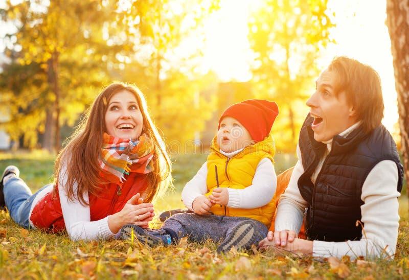 Il padre ed il bambino felici della madre della famiglia sull'autunno camminano in parco fotografia stock libera da diritti