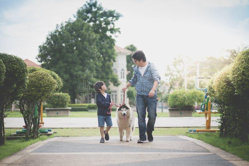 Il padre ed il figlio che camminano con un husky siberiano indossano nel parco immagini stock libere da diritti