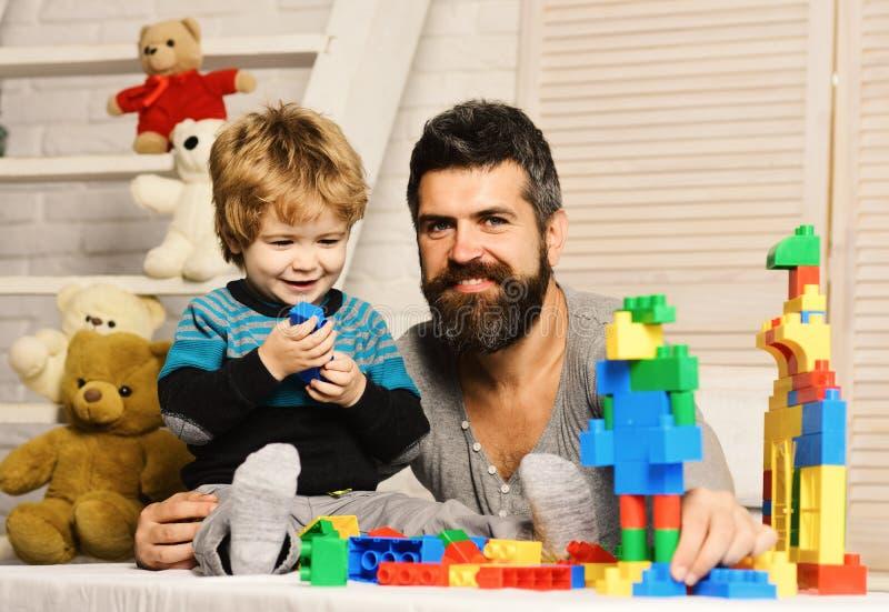 Il padre ed il figlio con i fronti sorridenti creano le costruzioni variopinte immagine stock