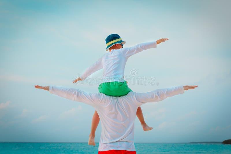 Il padre ed il figlio felici sulle spalle giocano al cielo fotografia stock libera da diritti
