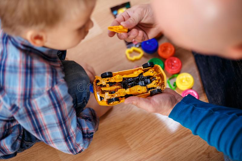 Il padre ed il figlio giocano con le lezioni delle macchine dei giocattoli con il bambino fotografia stock