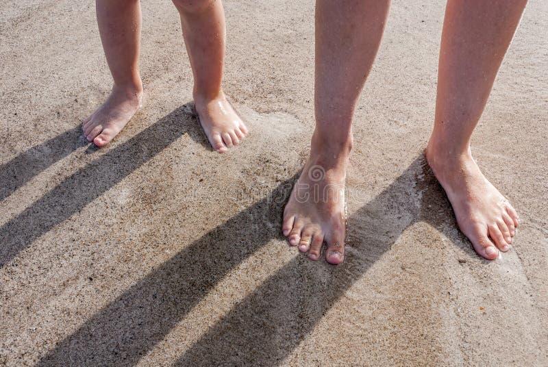 Il padre ed il figlio hanno messo i loro piedi nell'acqua su una vacanza di famiglia sulla spiaggia fotografia stock libera da diritti