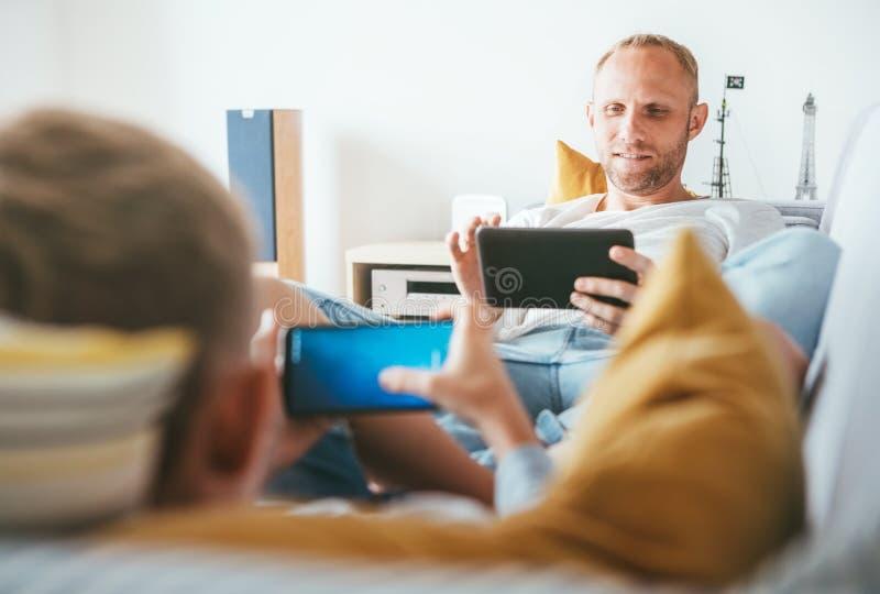 Il padre ed il figlio hanno passato il tempo libero con gli apparecchi elettronici: compressa a fotografia stock libera da diritti