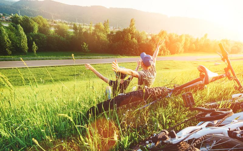 Il padre ed il figlio riposano insieme in erba verde quando abbia passeggiata della bicicletta immagine stock