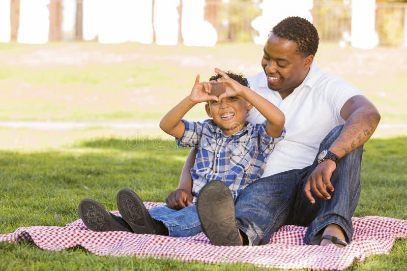 Il padre ed il figlio della corsa Mixed che fanno il cuore passano il segno fotografia stock libera da diritti