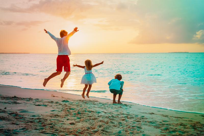 Il padre felice appassisce il gioco del figlio e del derivato sulla spiaggia immagine stock