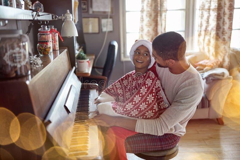 Il padre felice con la ragazza del bambino sul Natale gioca la musica sul piano fotografie stock