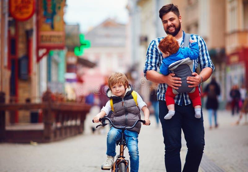 Il padre felice ed i due figli sulla città camminano Congedo parentale Bambino fotografia stock