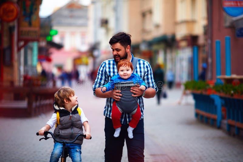 Il padre felice ed i due figli sulla città camminano Congedo parentale Bambino fotografia stock libera da diritti