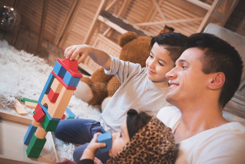 Il padre, il figlio e la piccola figlia del bambino stanno giocando con i cubi per i bambini alla notte a casa fotografia stock