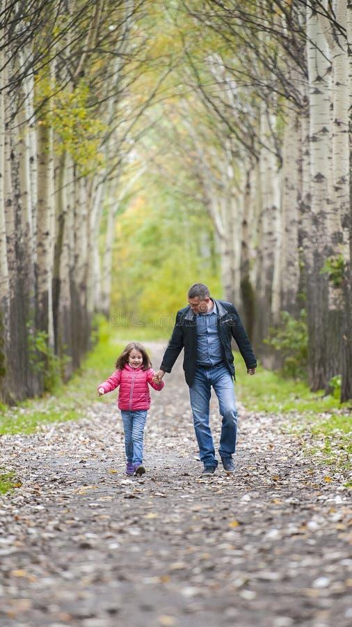 Il padre funziona con una figlia e tiene la sua mano sulla natura sulla vacanza del giorno di autunno Papà e ragazza che camminan immagine stock