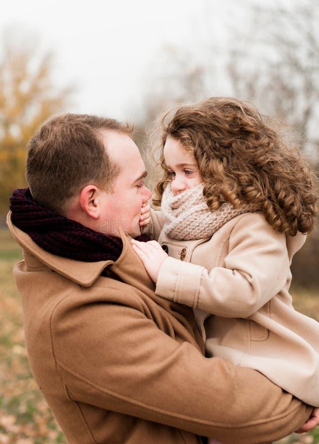 Il padre gioca con la sua piccola figlia riccia che la tiene nelle sue armi fotografia stock