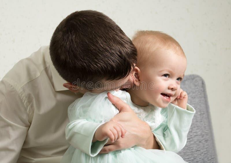 Il padre gioca con la sua piccola figlia, solletica il suo collo con i baci fotografia stock