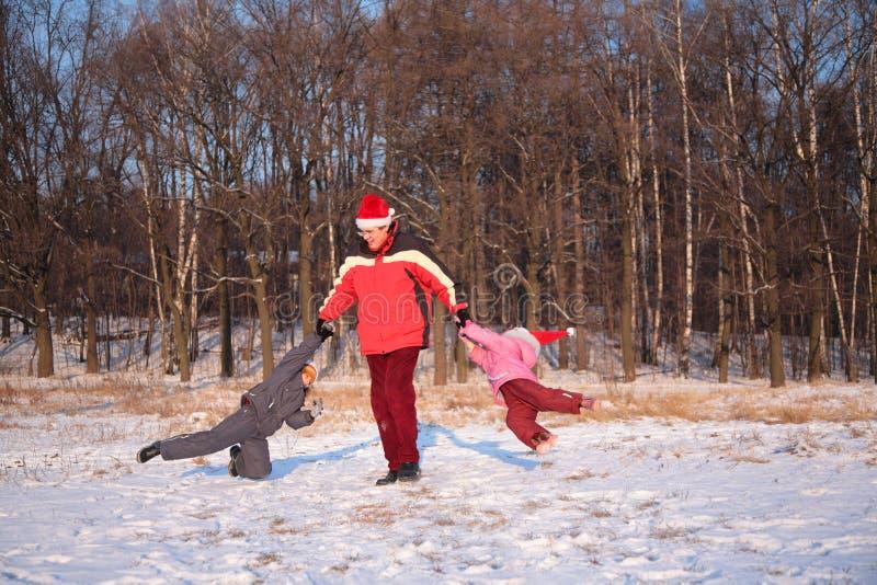 Il padre gira i bambini in inverno fotografia stock