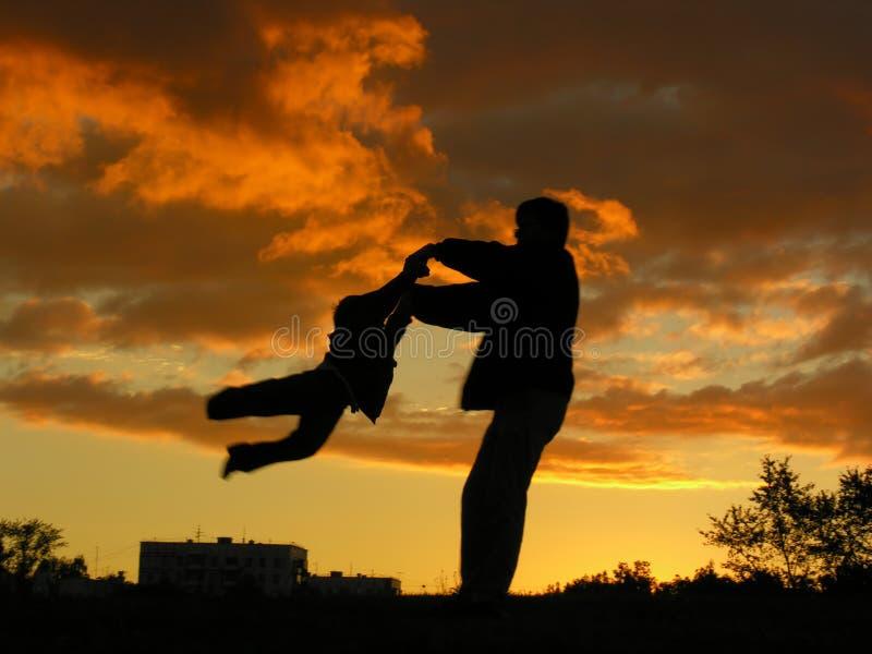 Il padre gira il tramonto del figlio fotografie stock