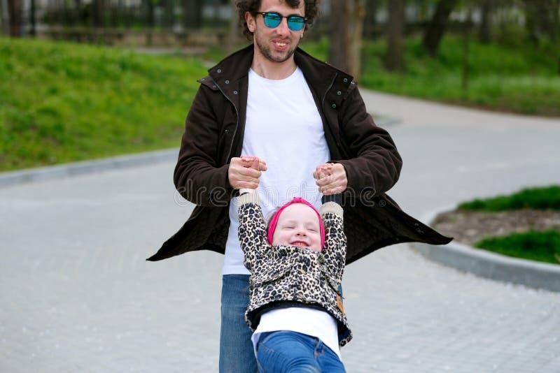 Il padre gira la piccola figlia in un parco verde immagine stock