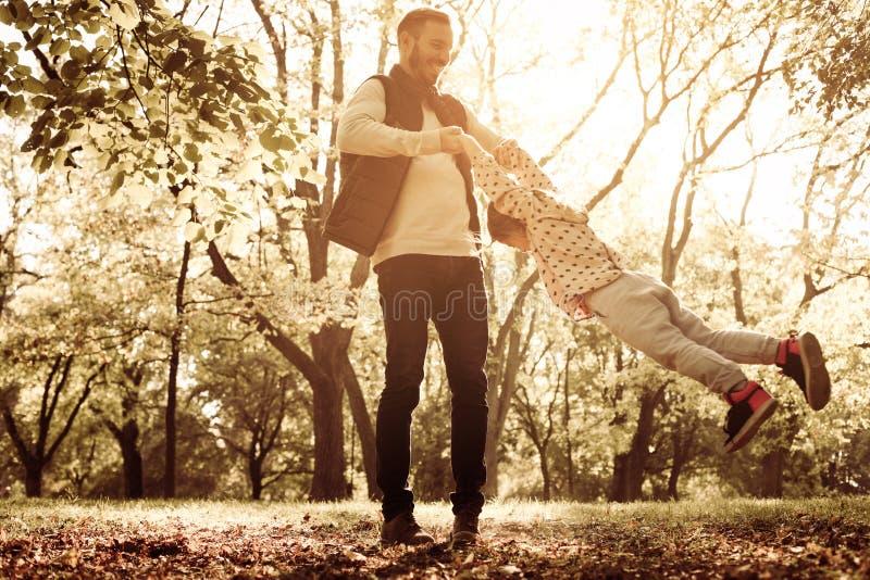 Il padre gira sua figlia nel cerchio e nel godere insieme immagini stock