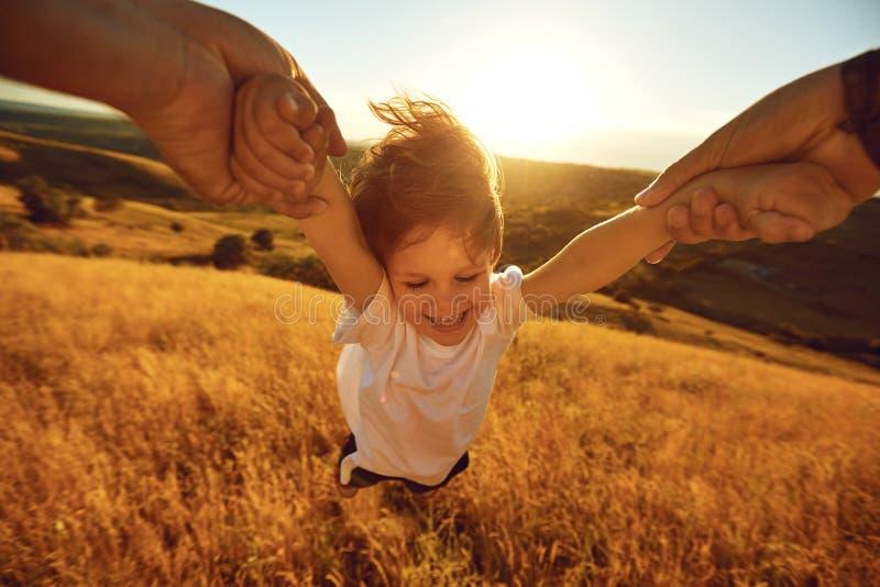 Il padre gira un bambino nel campo in natura fotografia stock