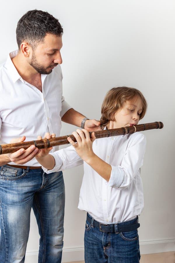 Il padre insegna al figlio a giocare la flauto di bambù immagine stock libera da diritti