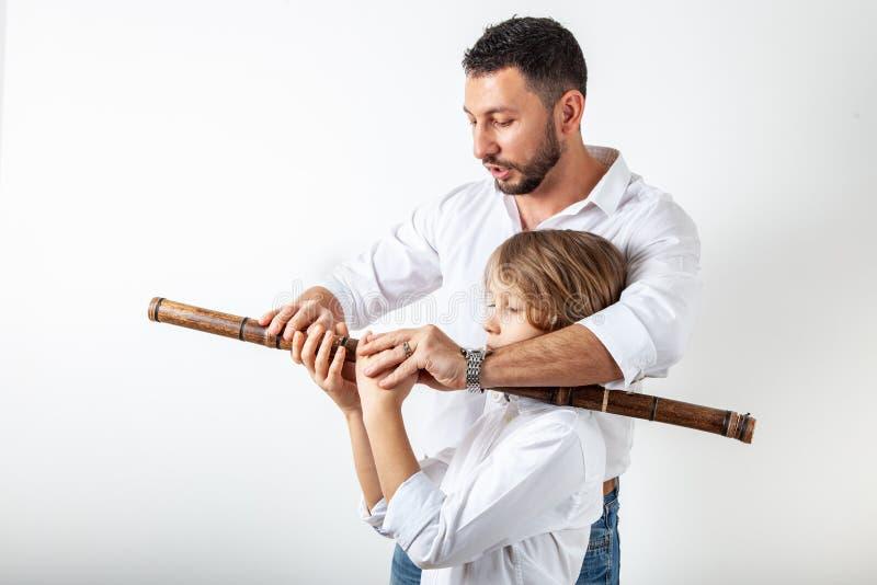 Il padre insegna al figlio a giocare la flauto di bambù fotografia stock libera da diritti