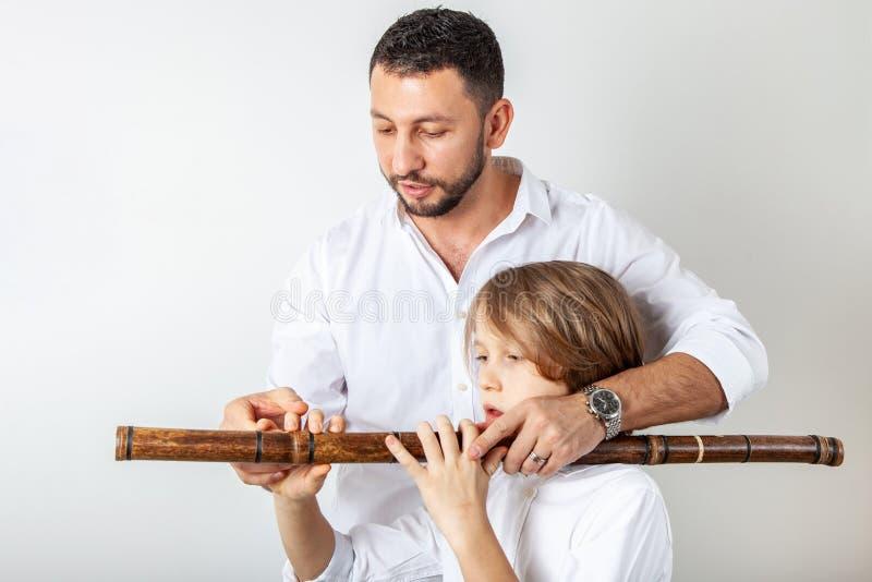 Il padre insegna al figlio a giocare la flauto di bambù immagine stock