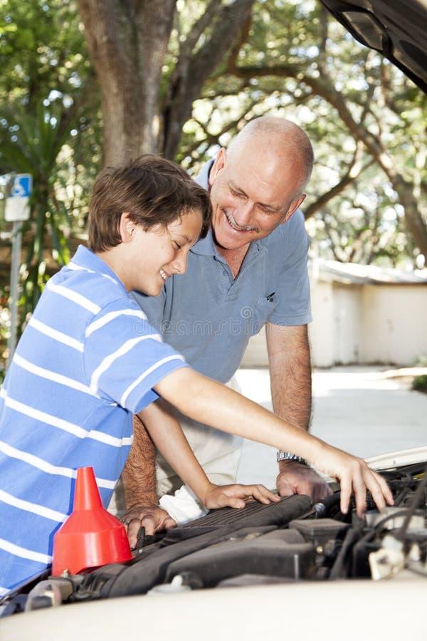 Il padre insegna al figlio a riparare l'automobile immagine stock libera da diritti