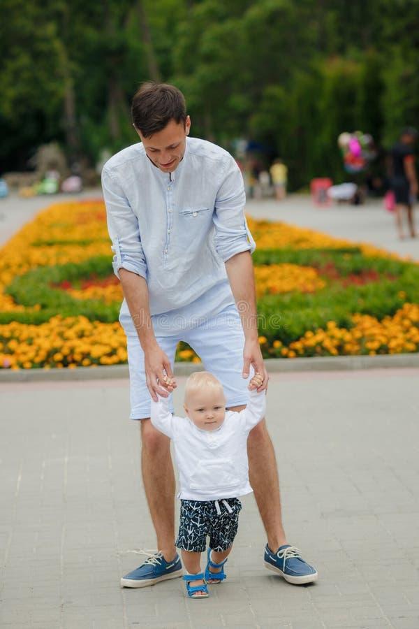 Il padre insegna a suo figlio a camminare immagine stock