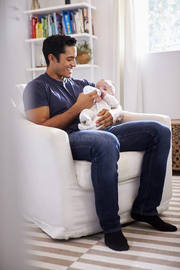 Il padre ispano sorridente che tiene suo figlio di quattro mesi gli alimenta una bottiglia, integrale, verticale fotografie stock