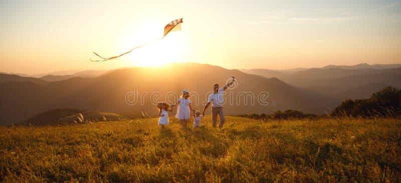 Il padre, la madre ed i bambini felici della famiglia lanciano l'aquilone sulla natura fotografia stock libera da diritti