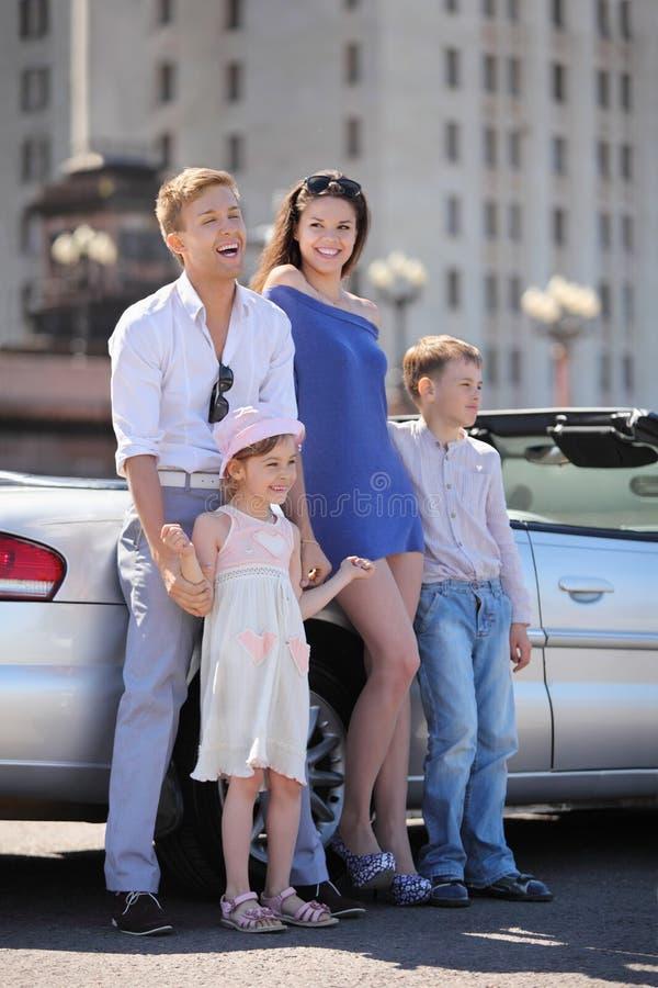 Il padre, la madre ed i bambini si levano in piedi l'automobile vicina fotografia stock