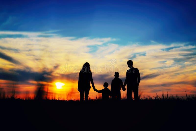 Il padre, la madre ed i bambini si tengono per mano su un fondo del tramonto fotografia stock