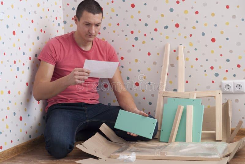 Il padre monta una sedia per i bambini immagini stock libere da diritti