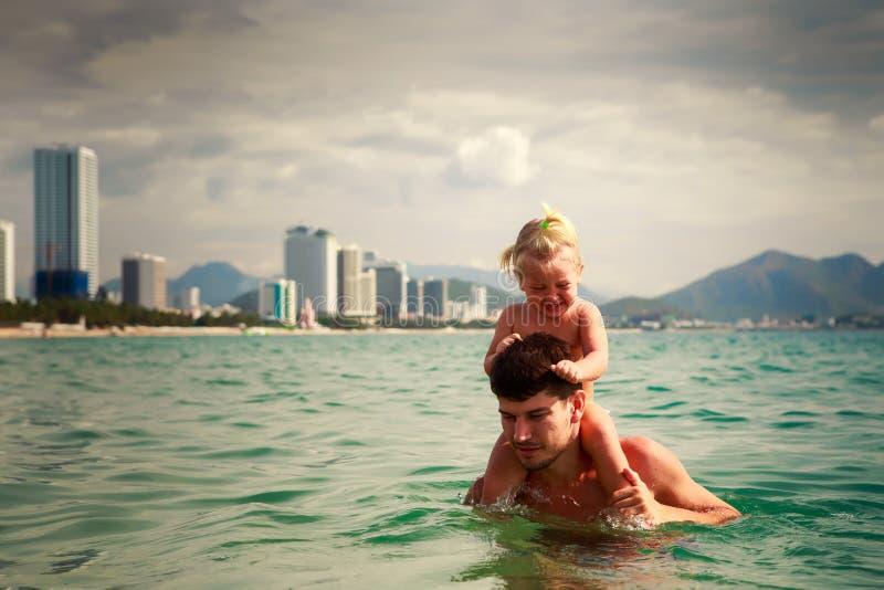 il padre porta la piccola figlia sulle spalle in acqua di mare fotografia stock
