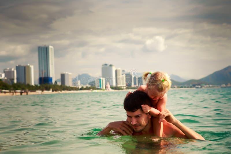 il padre porta la piccola figlia sulle spalle in acqua di mare fotografia stock libera da diritti