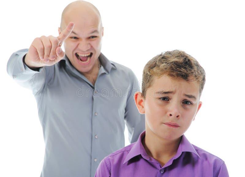 Il padre rigoroso punisce il suo figlio fotografia stock